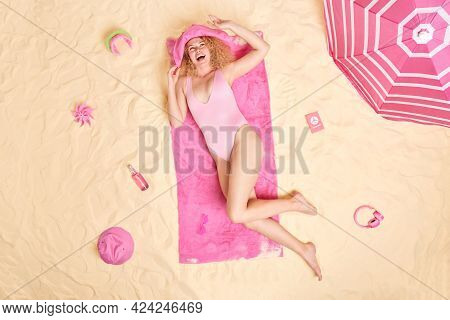 Summer And Relaxation Concept. Happy Slim Curly Woman In Bathing Suit Lies On Soft Towel Spends Unfo