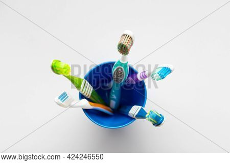 Toothbrushes In A Plastic Cup On A White Background. Concept Toothbrush Selection. Oral Cavity Care.