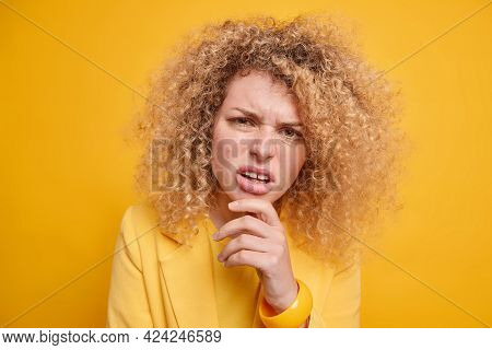 Close Up Portrait Of Displeased Young European Woman Holds Chin Looks With Indignant Expression Wear