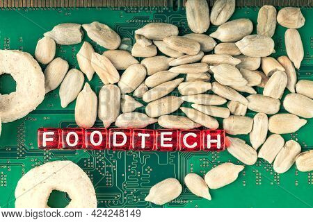 Foodtech Inscription On Red Cubes In White Letters On The Background Of A Microcircuit And Sunflower