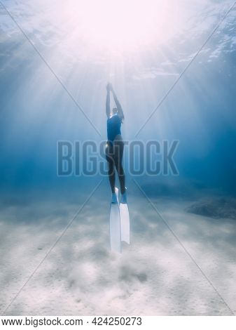 Female Freediver Glides With Fins Underwater In Ocean With Sunlight.