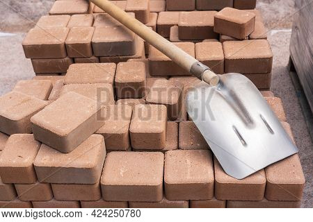 An Old, Shabby Shovel With A Wooden Handle Rests On A Neatly Folded Stack Of Light Ocher Paving Slab