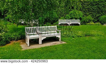 White Bench In Front Of The Image With Two Benches In The Background. There Is Grass All Over The Pi