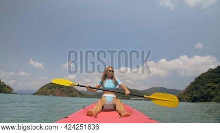 Sportive Woman Rows Pink Plastic Canoe Along Sea Water. Positive Sports Girl Hand Padding On Kayak,