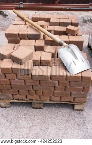 The Ocher-colored Paving Slabs Are Stacked In Neat Rows On A Wooden Pallet. On Top Is A Shovel With