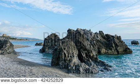 Scalea Beach, Calabria Region. Rocky Formations At The Beach. In The Background, On The Left, The Ta