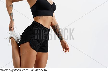 Low Section View Of Fit Young Woman Stretching Her Leg Before A Run In Fitness Studio, White Backgro