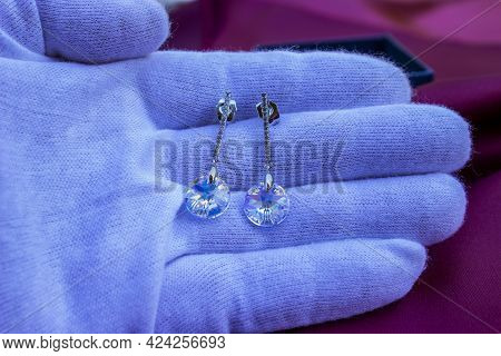 A White-gloved Hand Holds The Earrings. Jewelry Made Of Natural Stones.