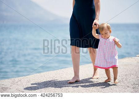 Mom Leads A Little Girl By The Hand Along A Concrete Breakwater