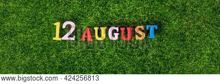 August 12. Image Of Wooden Colored Letters And Numbers On August 12 Against The Background Of A Gree