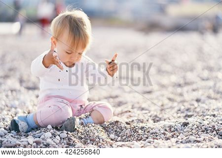 Cute Baby Sits On A Pebble Beach And Throws Small Pebbles