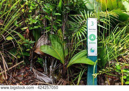 Praslin, Seychelles, 01.05.2021. Glacis Noir Nature Trail Signpost Among Lush Tropical Vegetation, P