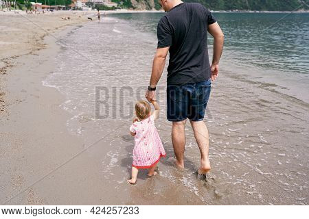 Dad Leads A Little Girl By The Hand Along The Sandy Shore