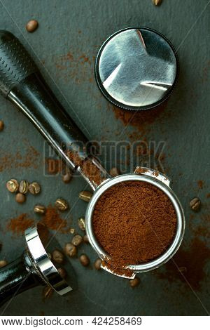Portafilter with coffee bean and temper on concrete table
