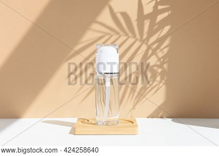 Reusable Glass White Bottle For Oil, Cream, Lotion Or Serum On A Beige Background With A Shadow Of T