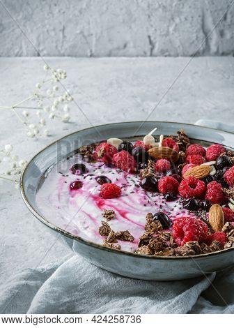 Healthy Breakfast Bowl With Yogurt, Granola, Muesli, Seeds, Frozen Raspberries, Blueberries, Nuts In
