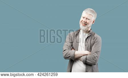 Positive Albino Guy With Folded Arms Looking And Smiling At Camera, Turquoise Background With Empty