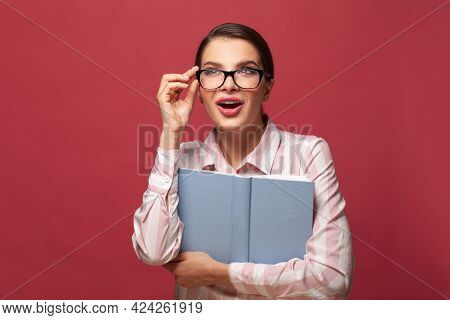 Portrait Young Happy Surprised Woman In Glasses Holds Book. Reading, Education, Studying And Learnin