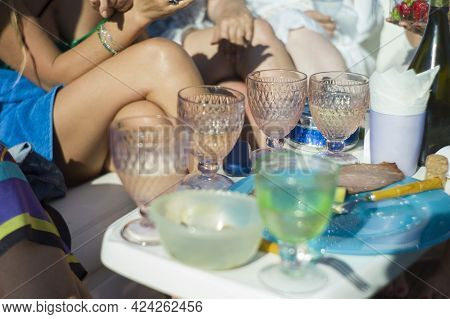 Champagne Glasses And Bare Female Legs Getting Tan In The Blurred Background, Outdoor Selective Focu