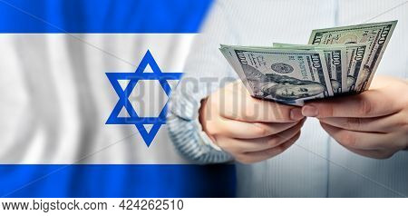 Israel Politics, Business And Social Problems Concept. Us Dollars Banknotes In Hand On Jewish Flag B
