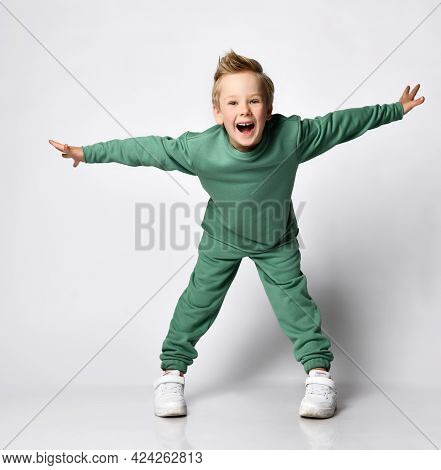 Portrait Of A Cheerful Little Boy Dressed In A Green Tracksuit. Cute Baby Posing On A White Backgrou