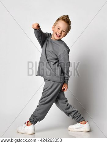 Little Boy With A Happy Smile, Turning Back And Pointing His Finger At The Camera, Studio Shot On A