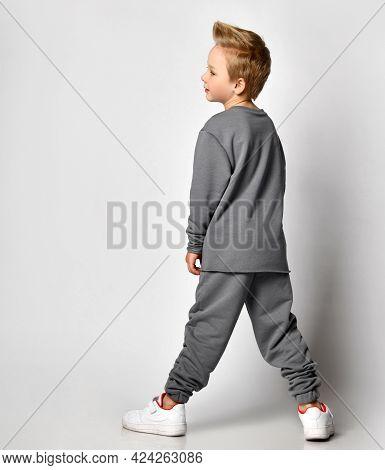 Little Blond Boy Child With European Appearance Wearing Trendy Sportswear Standing Backside And Look
