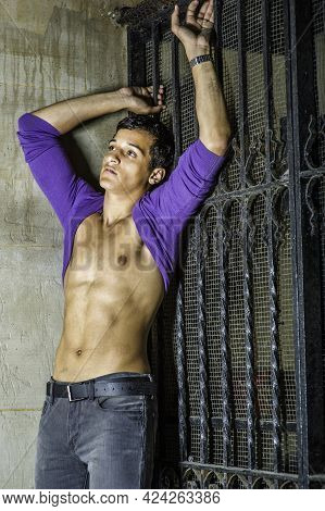Leaning On The Corner Between A Wall And A Metal Gate, A Sexy Young Guy Is  Rolling His Purple Sweat