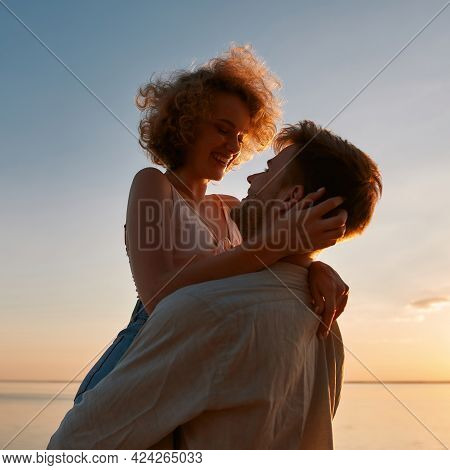 Portrait Of Happy Young Caucasian Man Raising Smiling Girlfriend On Beach At Sunset While Looking At