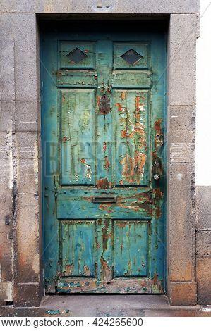 Old weathered timeworn shabby door in Funchal, Madeira island.