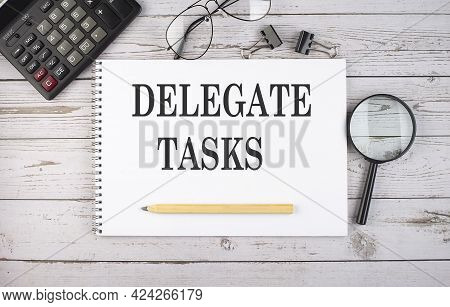 Blank Notebook With Text Delegate Tasks On White Background With Calculator And Office Tools.