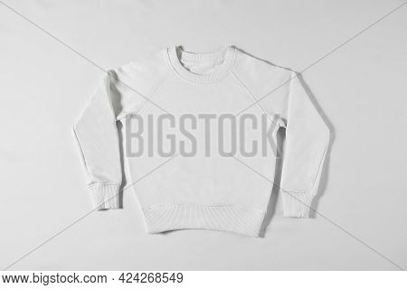 White Jacket Laying On A Light Background In The Studio. Stylish Clothing Concept. Sweatshirt For Br