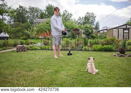 A Teenager Enjoys Weightlifting With Heavy Kettlebells In A Flowering Summer Garden. A Pug Puppy Sit