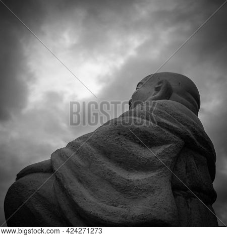 Contemplating Buddha With Dramatic Clouds In Black And White.