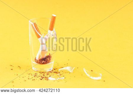 Two Crumpled And Broken Filter Cigarettes In A Broken Glass. Quitting Smoking