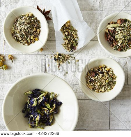 Bowls And An Envelope Of Dried Herbs And Loose Leaf Teas On A White Stone Surface