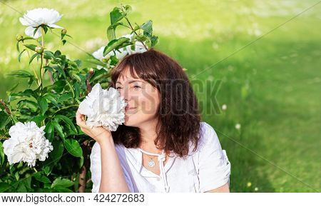 Portrait Nice Woman Of Forty Five Years Old With Brown Hair Sitting On Green Lawn In Sun And Sniffs