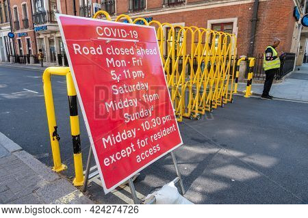 London, Uk - May 30, 2021: A Sign About Road Closures Due To Covid-19 With A Man Enforcing The Rules
