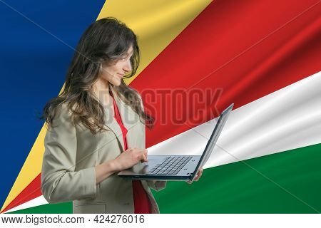 Freelance In Seychelles. Beautiful Young Woman Freelancer Uses Laptop Computer Against The Backgroun