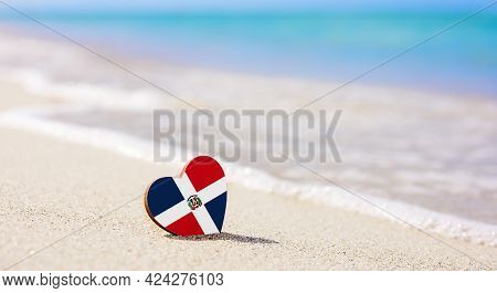 Flag Of The Dominican Republic In The Shape Of A Heart On A Sandy Beach. The Concept Of The Best Vac