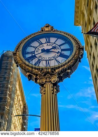 Fifth Avenue Building Street Clock With Flatiron Building In Blurry Background Under A Partly Cloudy