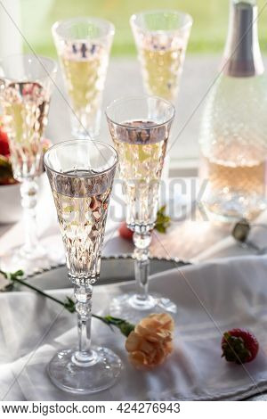 A Vertical View Of Several Tall Crystal Flute Glasses Filled With Sparkling Rose Wine, Back Lit Agai