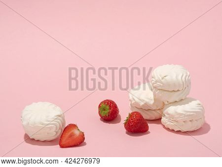 Marshmellows With Strawberries On A Baby Pink Background. Soft And Airy Photo In Pastel Colours.