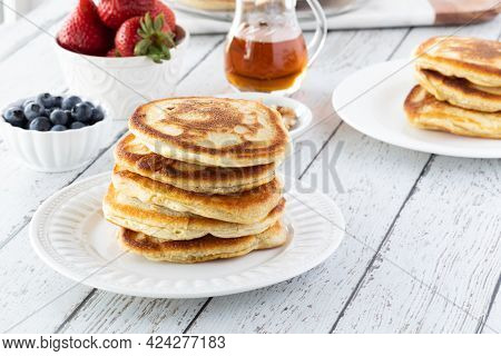 A Fresh Stack Of Warm Buttermilk Pancakes Ready For Toppings, On A Light Wooden Table.