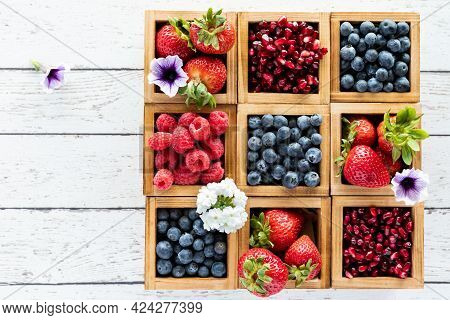Top Down Close Up View Of An Arrangement Of Berries In Wooden Compartment Boxes Against A Light Wood