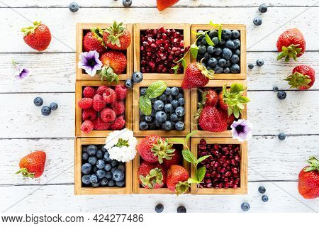 Top Down View Of Wooden Compartment Boxes Filled With Various Types Of Berries Against A Light Woode