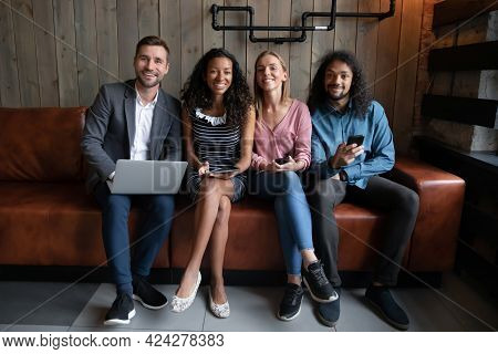 Happy Mixed Race Young People Using Different Gadgets.