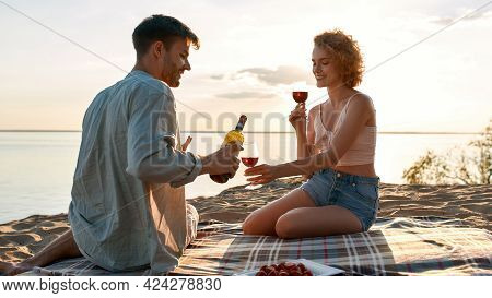 Happy Young Caucasian Couple Filling Glasses With Red Wine During Date On Beach In Evening, Widescre