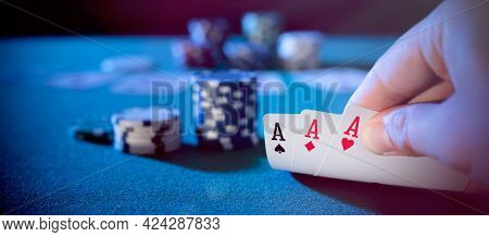 Hand Picks Up Cards, Three Aces, Plays Casino Poker. Background With Copy Space