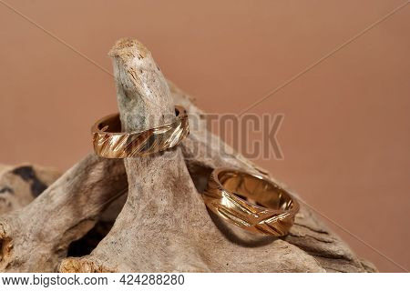 Closeup Of Two Classy Gold Rings With Notches Arranged On Wooden Element Over Beige Background. Jewe